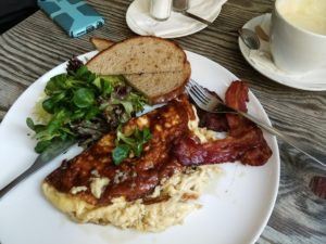 Breakfast with bacon, a burnt omelette, a salad and toast